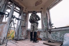 Man in military uniform looks out of the old window. stock photo