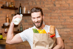 Man with milk and bag full of food. Handsome man holding milk with paper bag full of healthy food in the kitchen Stock Photo