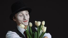 Man mime with a bouquet of flowers on a black background stock video footage