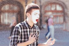 Man mime smokes a cigarette in the street. Man mime smokes a cigarette in town Stock Photos