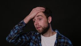 A Man Mimicing Against a Black Background. A young man immitating forgetfulness against a black background. Close-up Shot Royalty Free Stock Images