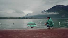 Man in a mint raincoat sits on a lake in the mountains near a moored boat of the same color. Rainy day. Lake Annecy. France 4k stock video