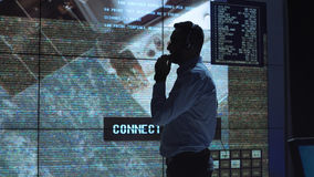 Man in mission control center. Silhouette of supervisor man standing near big screen in  flight control center watching satellite. Elements of this image Stock Photography