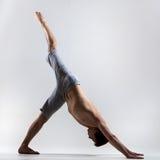 Man mit Beinen versehen verfolgen unten Yogahaltung Stockfotografie