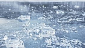 Man in the mittens smashes the ice on the ice. Slow motion. The camera moves behind the ice. A piece of ice is very. Beautifully broken about the icy with stock video footage