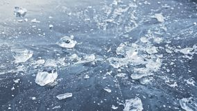 Man in the mittens smashes the ice on the ice. Slow motion. The camera moves behind the ice. A piece of ice is very. Beautifully broken about the icy with stock video