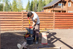 Man mixes cement with shovel in the bucket stock image