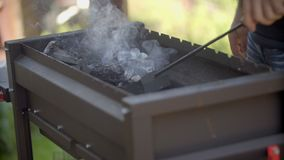 The man mixes coals in a brazier. the man stirs coals. the man mixes coals in a brazier an iron shovel. The man stirs stock video