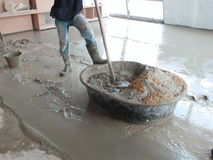 Man Mixing Cement. A man mixing cement in a metal tub at the construction site Royalty Free Stock Images
