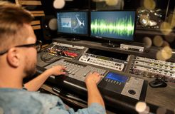 Man at mixing console in music recording studio. Music, technology, people and equipment concept - man at mixing console in sound recording studio over festive Stock Photography