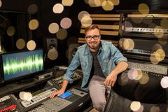 Man at mixing console in music recording studio. Music, technology, people and equipment concept - man at mixing console in sound recording studio over festive Stock Photo
