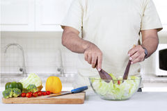 Man mixing salad on a bowl Royalty Free Stock Image