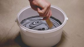 Man mixing two paint colors in bucket. Light grey with black to make the color darker stock video footage