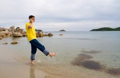 Man and mobile. Coast.The young man talks on mobile and does(makes) splashes by a leg(foot Stock Photos