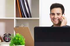 Man with mobile and computer. Man smiling looking at camera with the phone mobile in front of the computer with them documents Stock Image