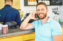 Man mobile conversation cafe barista background. Drink coffee while waiting. Coffee take away option for busy people. Man with smartphone order coffee. Coffee stock photography