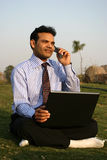 Man on mobile with laptop. Indian man with laptop talking on a cell phone Stock Photo