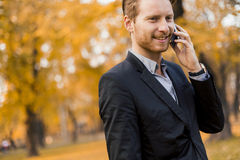 Man with mobile phone in the autumn park Royalty Free Stock Photo