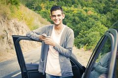 Man with mobile phone in the car. Young man with mobile phone in the car Stock Photography