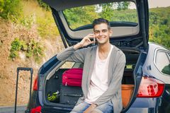Man with mobile phone in the car. Young man with mobile phone in the car Royalty Free Stock Images