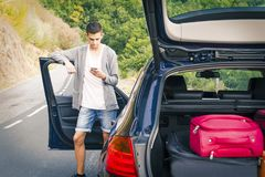 Man with mobile phone in the car. Young man with mobile phone in the car Royalty Free Stock Photo