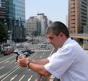 Man with mobile phone in a city. Man using a mobile phone to read an email in a modern city Royalty Free Stock Photo