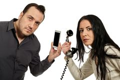 Man with a mobile phone communicates with woman with a vintage p Royalty Free Stock Image