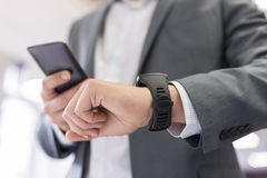Man with Mobile phone connected to a smart watch. Businessman looking at his connected watch Royalty Free Stock Photo