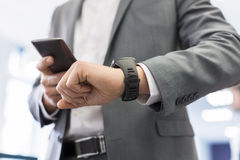 Man with Mobile phone connected to a smart watch. Businessman looking at his connected watch with cell phone Royalty Free Stock Images