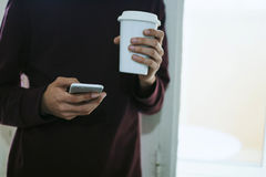 Man with the mobile phone and the cup. Young man with the mobile phone and the cup of coffee in the window Stock Photos