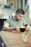 Man with mobile phone drinking beer Stock Photos