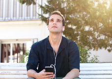 Man with mobile phone and earphones looking up Royalty Free Stock Photos