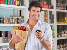Man With Mobile Phone And Grocery Paper Bag Royalty Free Stock Images