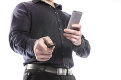 Man with a mobile phone in the hands using car key isolated on white Royalty Free Stock Photo