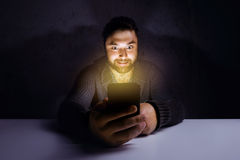 Man mobile phone mad concept. Mad man with mobile phone in dark room Stock Image