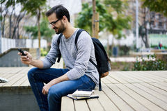 Man with mobile phone making online shopping on web store paying on banking service. Skilled male international student resting during break in university using stock images