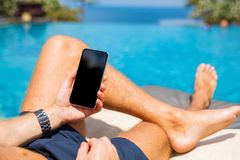 Man with mobile phone by the pool. Man using mobile phone by the pool stock image