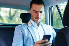 Man with mobile phone sitting in car and typing text message. Young businessman with mobile phone sitting in car and typing text message Royalty Free Stock Photo