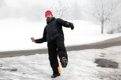 Man with mobile phone is slipping on a freezy street Royalty Free Stock Images