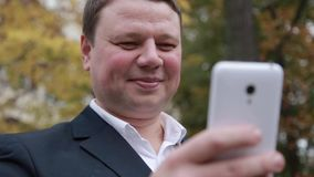 A man with a mobile phone smartphone in his hands stock footage