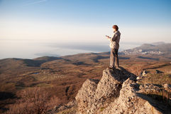 Man with mobile phone on the top of world Royalty Free Stock Images
