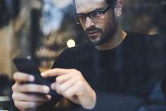 Man with mobile phone using wireless internet connection to confirm or sent upgrading Royalty Free Stock Images