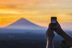 Man with Mobile Phone and Volcano Agung as Background. Stock Image