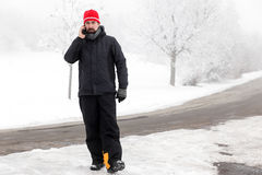 Man with mobile phone is walking across a icy street Royalty Free Stock Photo