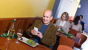 Man with mobile at the table in cafe Stock Images