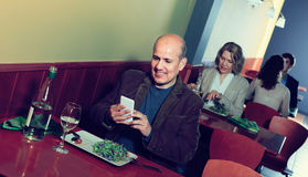 Man with mobile at the table in cafe Royalty Free Stock Photo