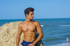 Man at the beach with defined body. Body statue of the model sunbathing Stock Images