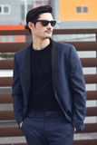 Man, model of fashion, wearing modern suit and sunglasses. Stock Image