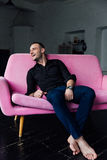 Man model sits on pink sofa in loft interior. Businessman in a black shirt and watch, blue pants. Barefoot. lies on the couch Royalty Free Stock Photos