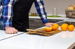 A man in a modern kitchen cuts juicy fruits oranges, a healthy lifestyle stock photo